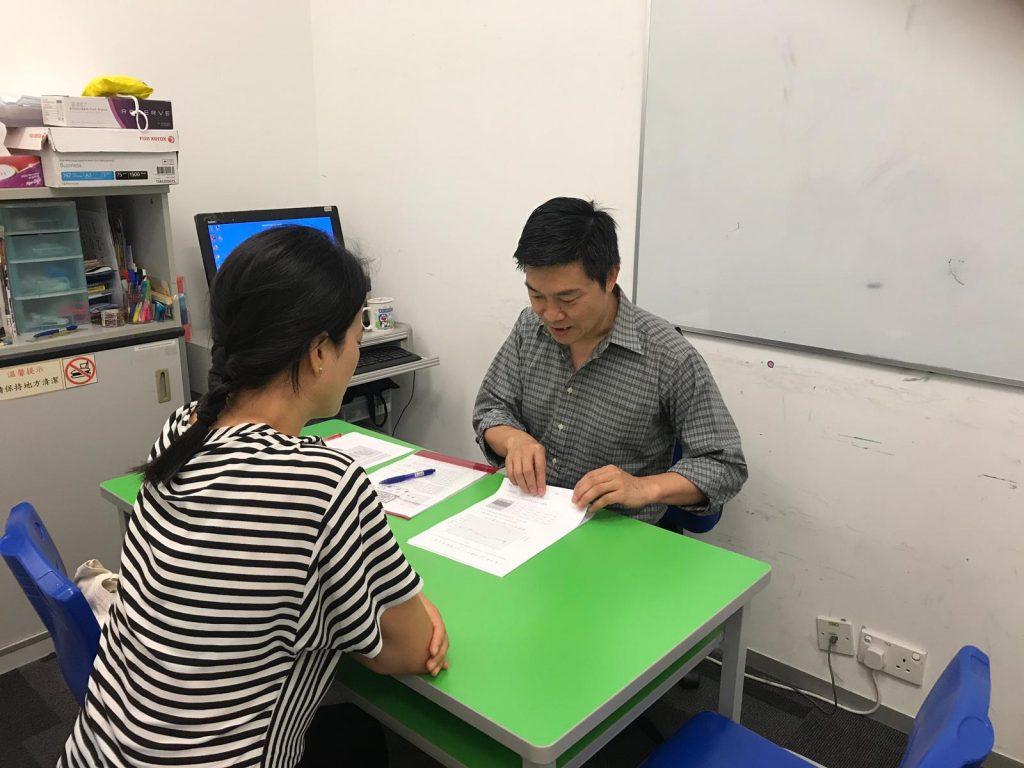 陳sir於家長日與家長討論學生的表現。